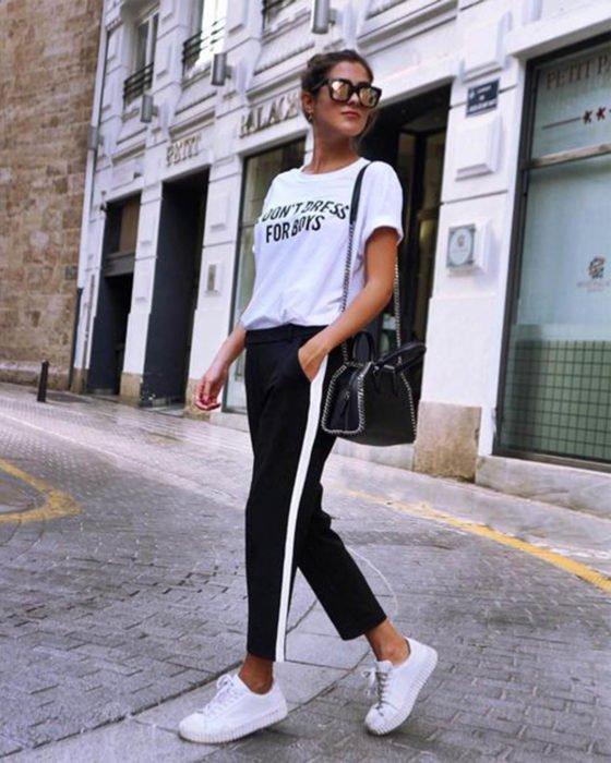 Chica usando un atuendo en color blanco y negro mientras camina por la calle