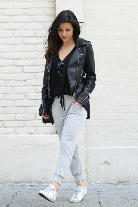 Chica usando un pants de color gris con chaqueta de cuero y blusa negra