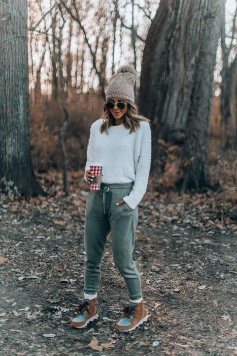 Chica usando un pants de color verde con un blusón de color beige