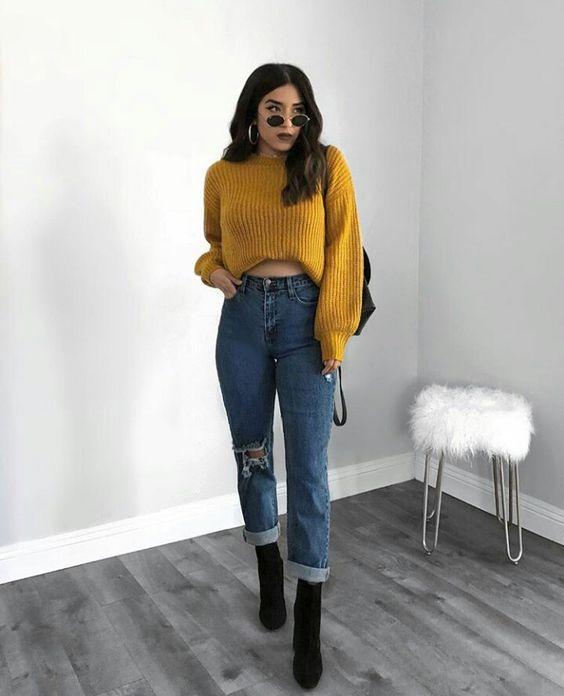 Chica usando jeans, botines negros y un abrigo de color mostaza