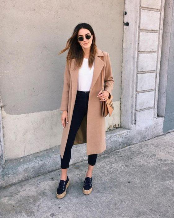 Chica usando un abrigo de color beige con jeans negros y blusa blanca