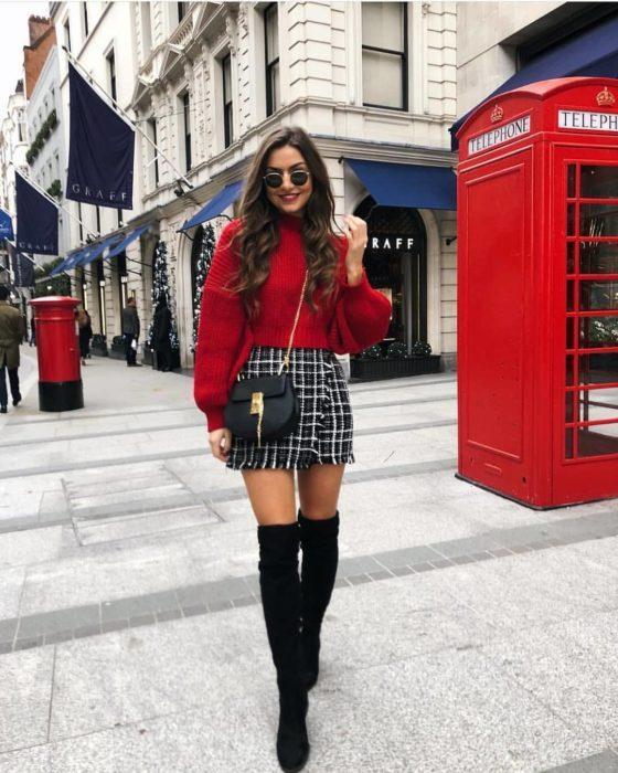 Chica usando una falda tipo escoces con un suéter de color rojo y botas altas