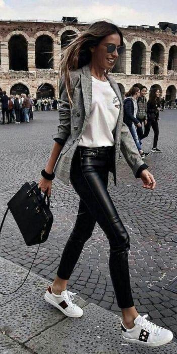 Chica usando unos pantalones de cuero negros, camisa y tenis blancos con un blazer de color gris