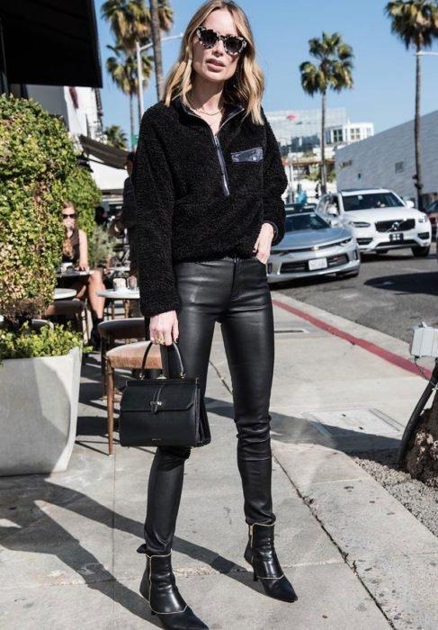 Chica usando una sudadera de color negro con un pantalón de cuero de color negro