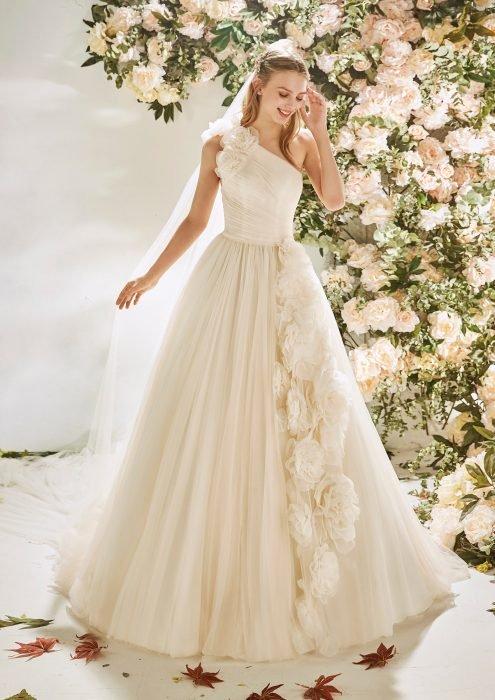 Chica con un vestido de novia en color blanco con flores en la parte de la falda