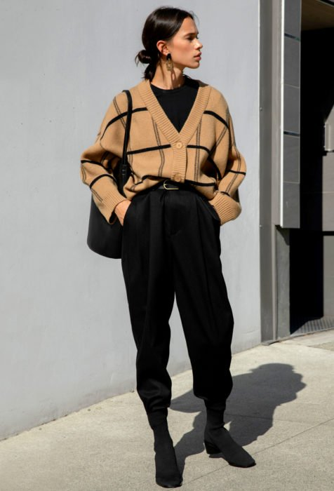 Looks con baggy jeans; Mujer con peinado de chongo bajo, con cardigan café de cuadros y pantalón negro oversized