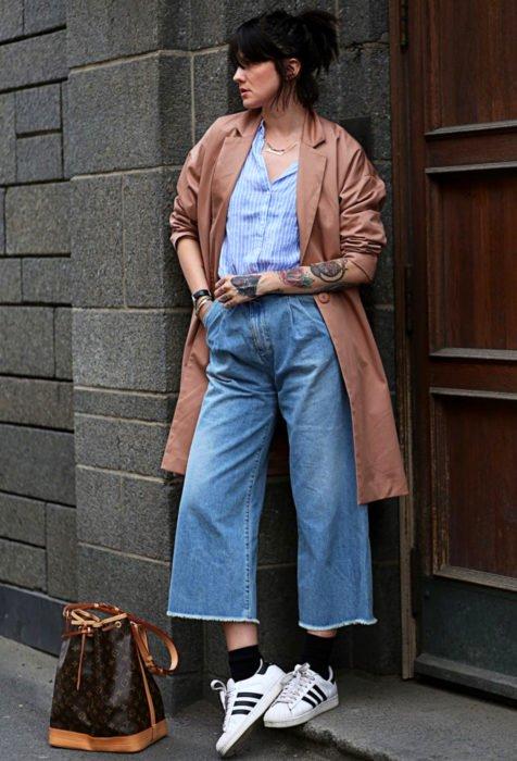 Looks con baggy jeans; chica en el pórtico de un edificio, con saco largo, tenis blancos y pantalón holgado, tatuajes en los brazos, peinado de media cola de cabello corto