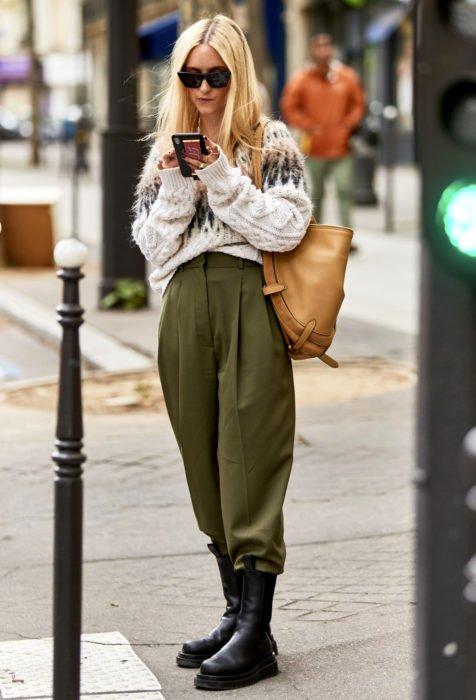 Looks con baggy jeans; mujer rubia mirando su celular en la calle, lentes oscuros, suéter tejido holgado, pantalón verde olivo oversized y botas negras