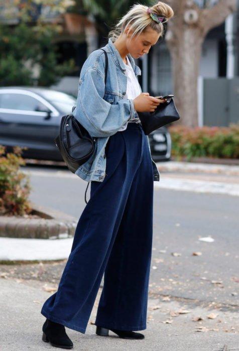 Looks con baggy jeans; mujer rubia mirando su celular en la calle con pantalones holgados y peinado de chongo alto