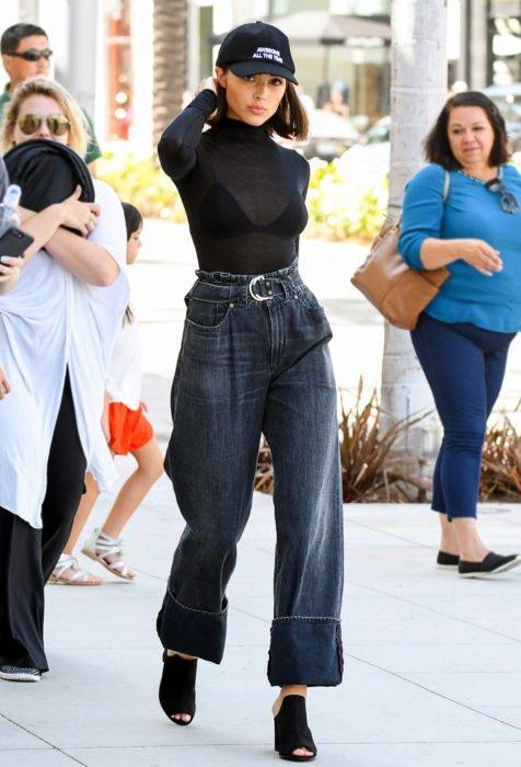 Looks con baggy jeans; chica con gorra, blusa transparente, pantalón oversized y botines
