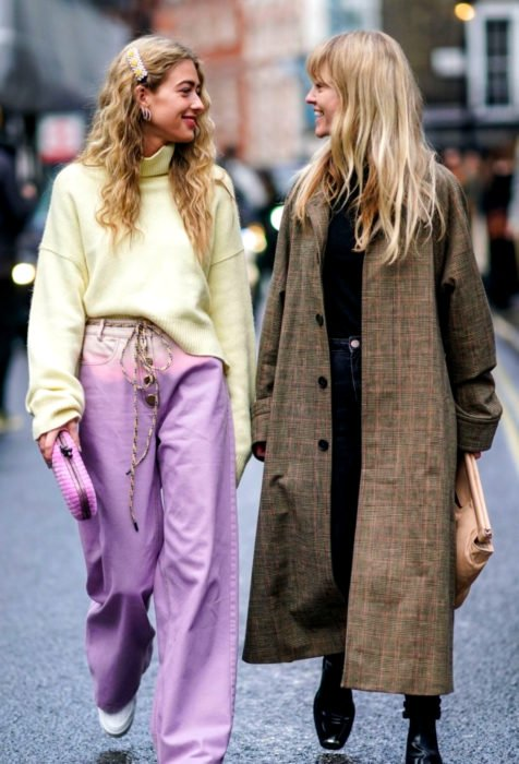 Looks con baggy jeans; amigas caminando en la calle y riendo, mujeres rubias con suéter oversized amarillo, pantalón holgado color lavanda, saco hasta los tobillos