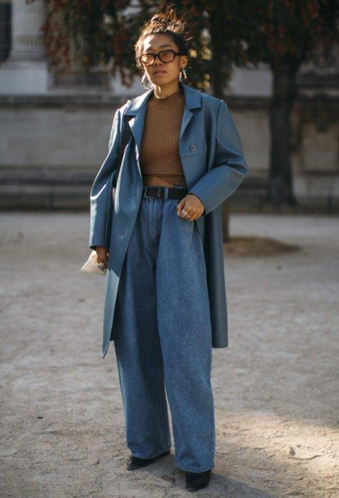 Looks con baggy jeans; mujer morena de ojos rasgados con peinado de chongo alto y despeinado, con pantalones holgados y saco oversized