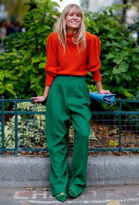 Looks con baggy jeans; mujer rubia vestida con colores contrastantes y brillantes, anaranjado y verde, con pantalón holgado y suéter oversized, bolsa azul