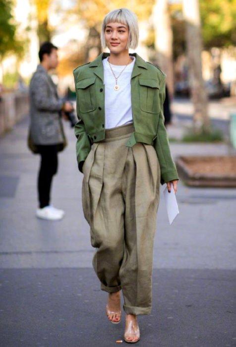 Looks con baggy jeans; mujer con corte de honguito, cabello rubio y fleco, con pantalón y saco oversized