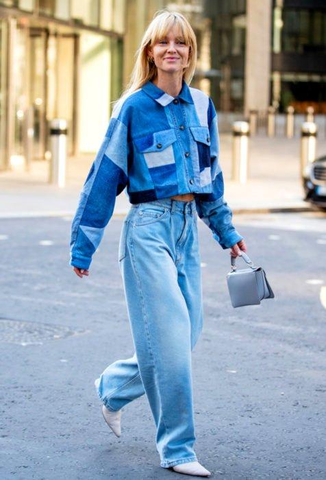 Looks con baggy jeans; mujer rubia caminando en la calle con pantalón oversized y chamarra de mezclilla, bolsa de mano mini