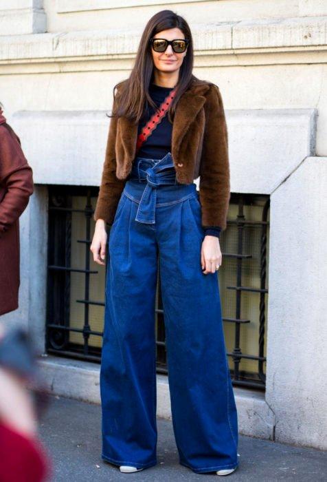 Looks con baggy jeans; mujer de cabello castaño, lacio y largo, con lentes de sol, abrigo café, pantalones oversized acampanados
