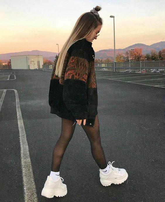Chica con tenis de plataforma altos y chaqueta negra