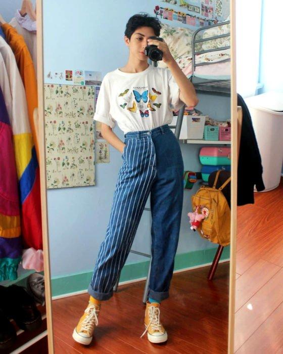 celestialyouth, joven recrea atuendos vintage de Sailor Moon; chico tomándose selfie frente al espejo con cámara profesional, playera blanca con estampado de mariposas, pantalón con una pierna rayada y la otra lisa, converse anaranjados
