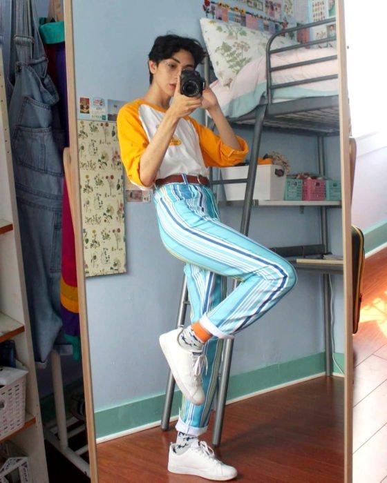 celestialyouth, joven recrea atuendos vintage de Sailor Moon; jeans rayados, tenis blancos, playera blanca con mangas anaranjadas, chico tomándose selfie frente al espejo