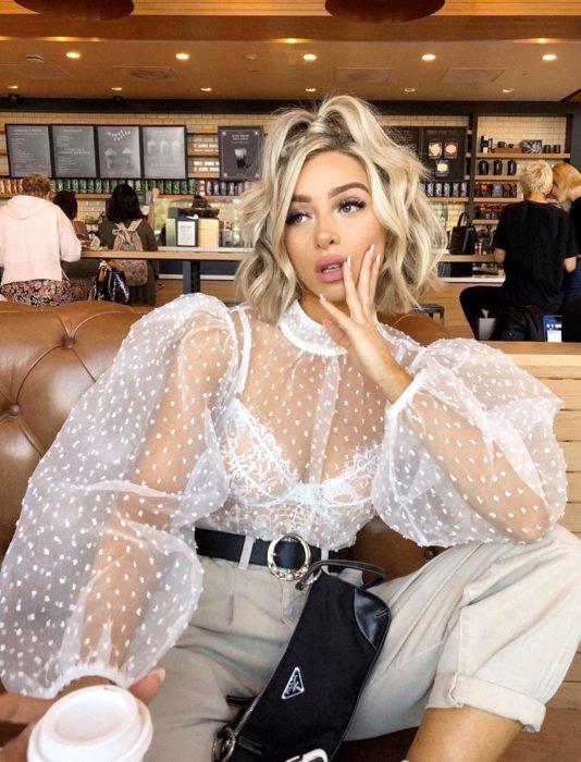 Chica rubia en un café con blusa blanca de tul y mangas gigot