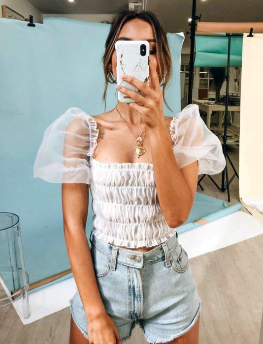 Mujer tomándose selfie frente al espejo con top blanco de mangas gigot y short