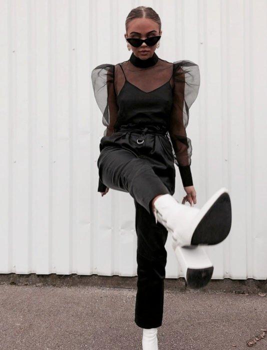Mujer con botas blancas y blusa con transparencias y mangas gigot