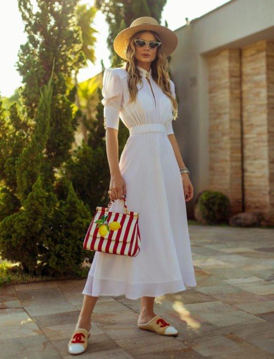 Mujer rubia con vestido largo, blanco de mangas gigot y sombrero