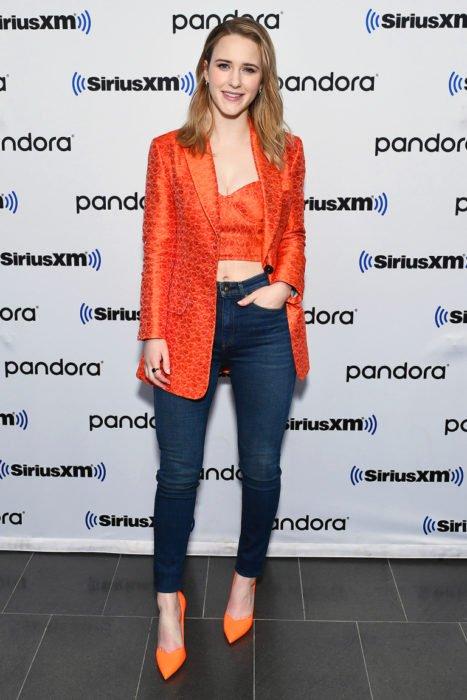 Chica usando un blazer y top de color naranja con unos jeans y stilettos naranja