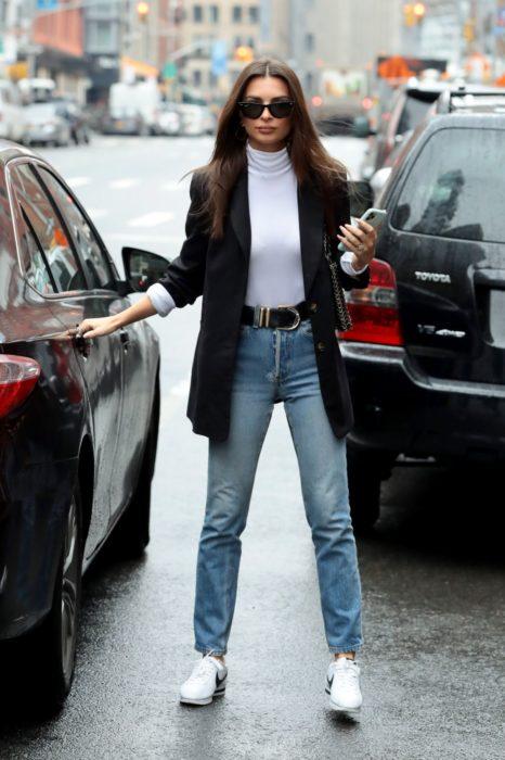 Chica usando un look de blazer con jeans mientras está a punto de subirse a un auto
