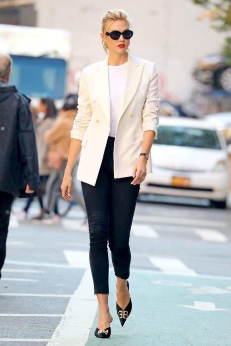Chica usando un blazer de color blanco con jeans negros