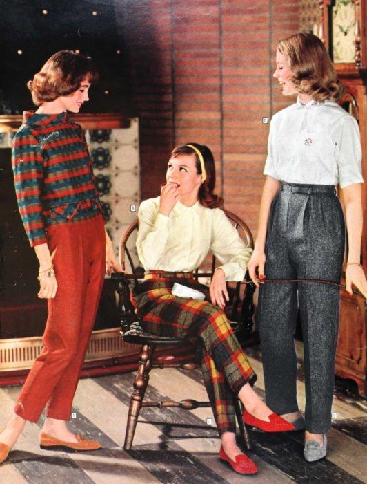 Moda femenina de los 70; tres amigas hablando y riendo; pantalón gris, de ciadros rojos y amarillos, blusa blanca y abrigo de patrones, flats anaranjados y grises; ropa y peinado retro