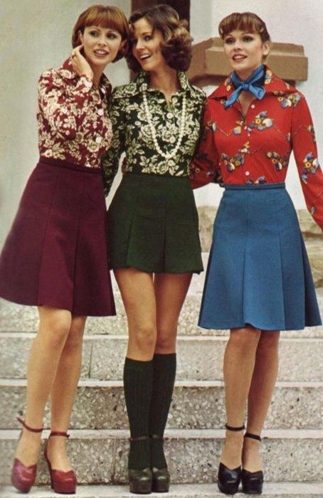 Moda femenina de los 70; tres amigas abrazándose, con blusas floreales guinda, verde y roja, y faldas a la rodilla color vino y azul, zapatillas de tacón con calcetas; ropa y peinados retro