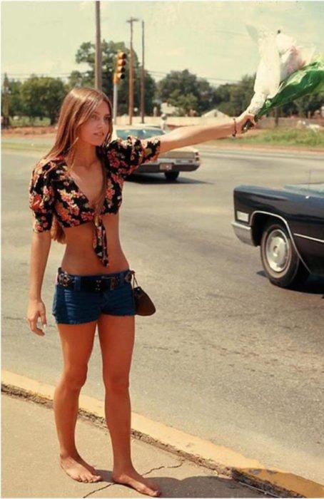 Moda femenina de los 70; mujer pidiendo rait con un ramo de flores, short a la cadera, tio negro floral, descalza; ropa y peinado retro