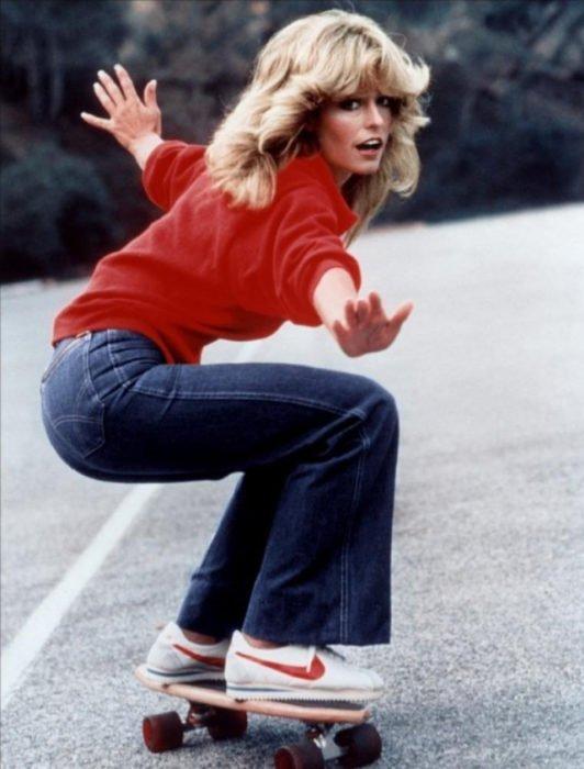 Moda femenina de los 70; Farrah Fawcett en patineta con suéter rojo; peinado retro