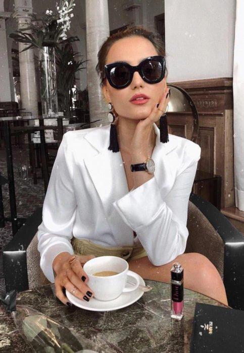 Outfit con blusa blanca; mujer con lentes oscuros, aretes de flecos tomando un café