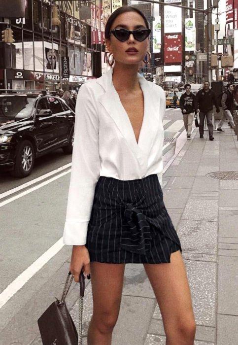 Outfit con blusa blanca; mujer en las calles de la ciudad con lentes oscuros, camisa y minifalda rayada