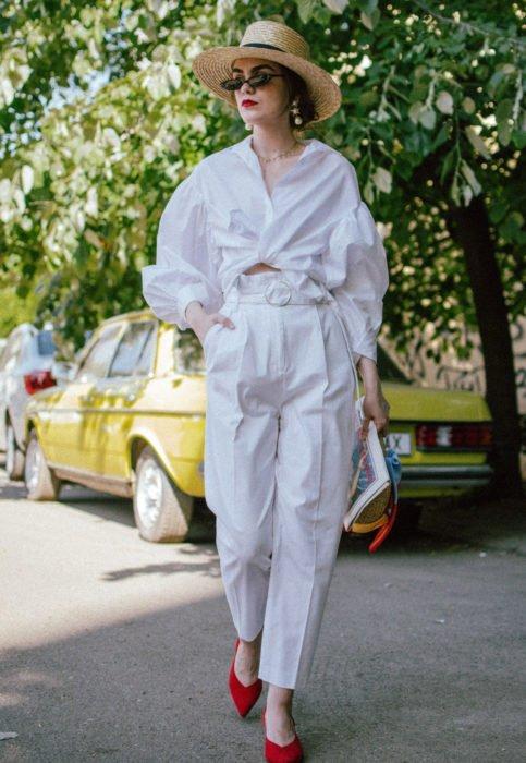 Outfit con blusa blanca; mujer caminando en la calle con sombrero de mimbre, camisa oversized, pantalón blanco y zapatillas rojas