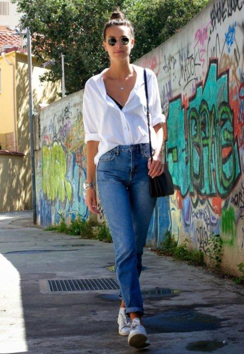 Outfit con blusa blanca; atuendo casual, camisa desfajada, mom jeans y tenis; mujer caminando en la calle frente a barda con grafitti
