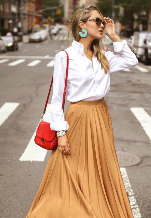 Outfit con blusa blanca; mujer rubia con lentes de sol, aretes grandes, camisa y falda anaranjada