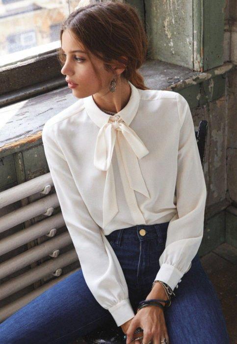 Outfit con blusa blanca; mujer mirando por la ventana con camisa marfil y moño en el cuello
