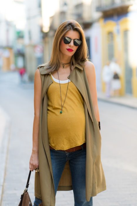 Chica embarazada usando una blusa de color mostaza con jeansy un chaleco largo