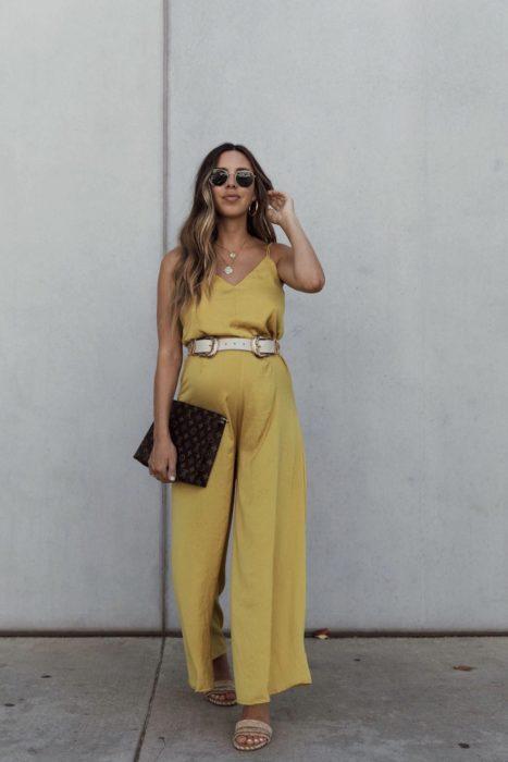 Chica embarazada usando un palatzo de color amarillo con un cinto en la parte de la cintura