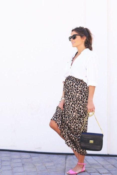 Chica embarazada usando un vestido de leopardo con una camisa de color blanco