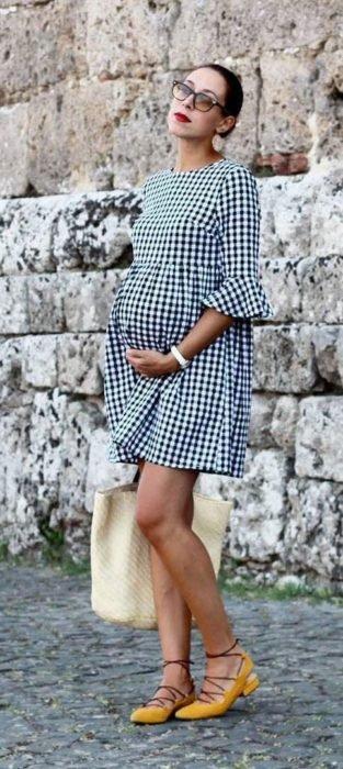 Chica embarazada usando un vestido de color girs con cuadros y sandalias de color amarillo