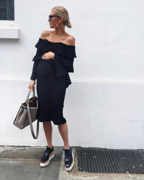 Chica embarazada usando un vestido de color negro con zapatos de plataforma