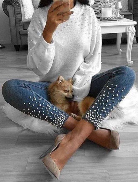 Jeans con perlitas en la zona de la pantorrilla y suéter blanco con perlitas en la sona del pecho