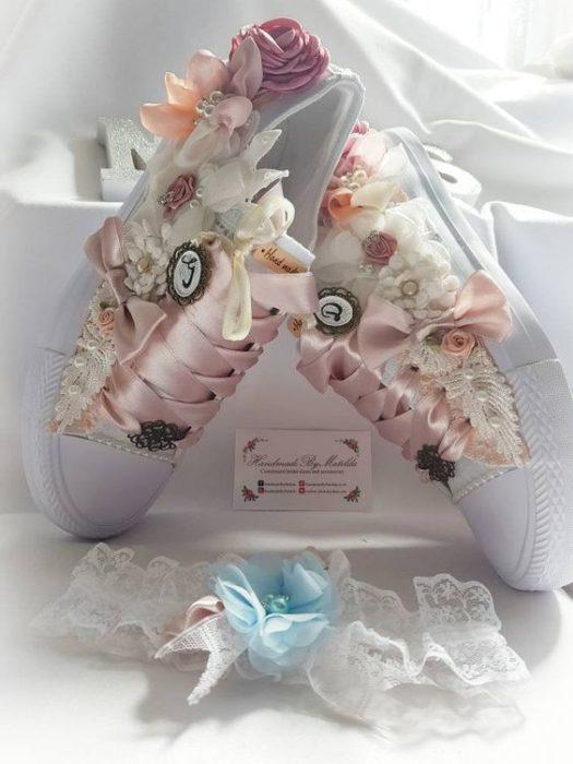 Tenis blancos con flores a lso costados y cintillas de listón rosa pastel para bodas