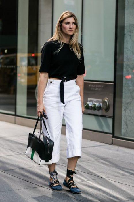 Chica rubia con blusa negra y pantalón blanco camina en la calle con bailarinas azules