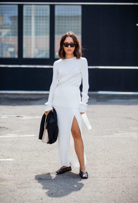 Mujer con vestido largo y blanco posa con sus bailarinas negras y lentes de sol