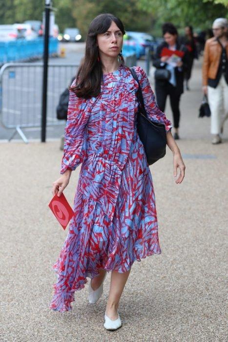Mujer de melena larga usa vestido largo con estampado azul y rojo con bailarinas blancas